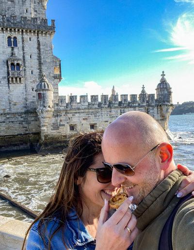 Joli couple dégustant un pastel de Nata devant la Tour de Belém lors d'une belle journée ensoleillée