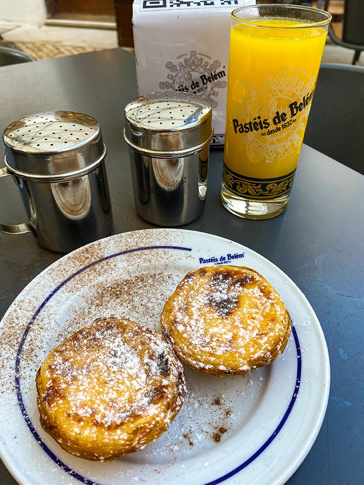 Deux pasteis de Belém saupoudrés de sucre et de canelle dans une assisette, accompagnées d'un jus d'orange dans la célèbre boutique, Pasteis de Belém, à Lisbonne.