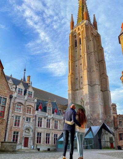 un jeune couple contemple la flèche de l'église Notre -Dame de Bruges.