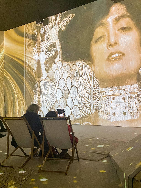 deux personnes dans des transats regardent le show mapping vidéo à l'exposition Klimt de Bruxelles