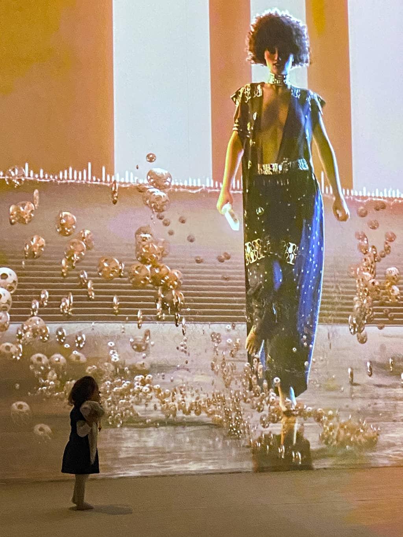 Une petite fille devant le grand écran projetant les oeuvres de Klimt lors de l'expostion immersive de Bruxelles