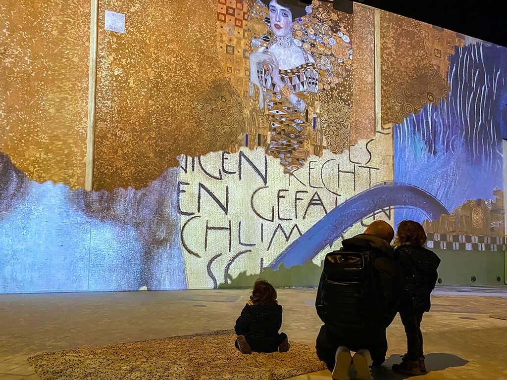 une petite famille installée sur un tapis regarde le show immersif à l'expo Klimt de Bruxelles