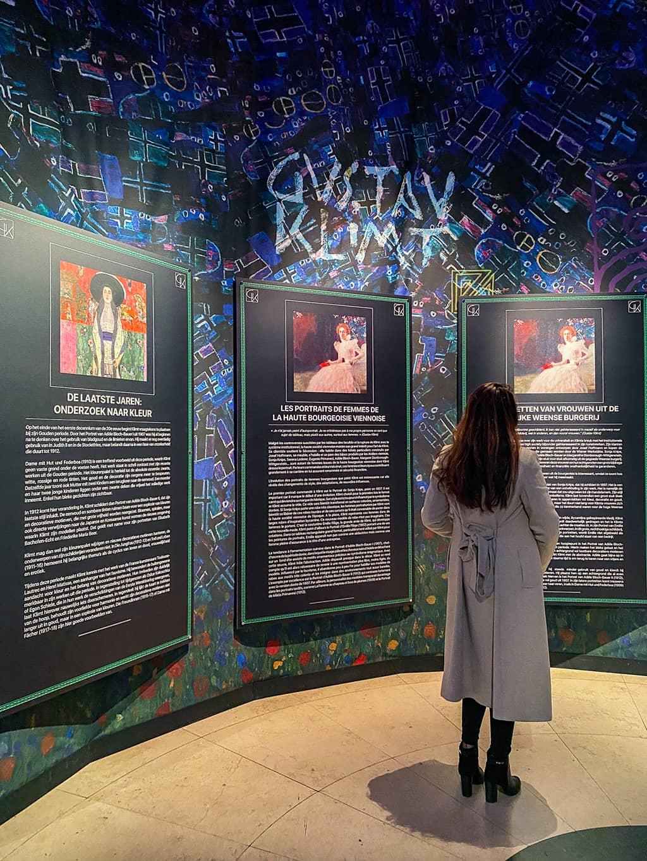 Une jeune femme lit les panneaux explicatifs à l'exposition Klimt de Bruxelles