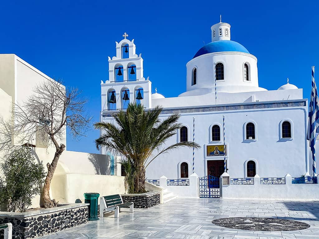 Une église au clocher bleu et aux murs blancs sur l'île de Santorin
