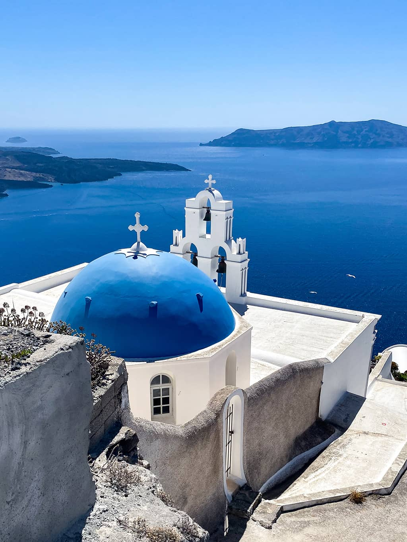 une chapelle au toit bleu surplombe la mer sur l'île de Santorin