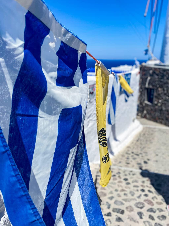 Drapeau grec flottant au vent sur l'île de Santorin.