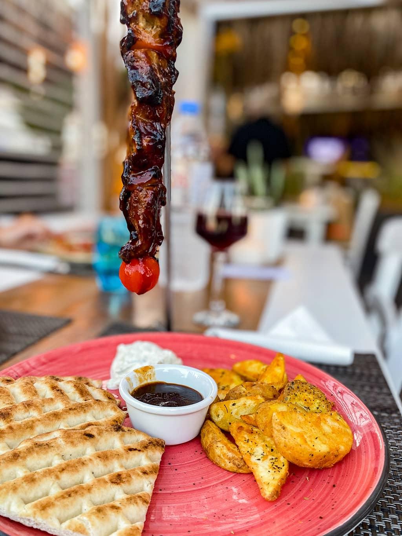 Brochette de porc suspendue avec des pommes de terre et pain grec au restaurant Alismari de Kamari sur l'île de Santorin